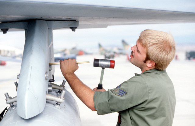 SGT Haid tightens a panel on an F-16 fighter aircraft on the flight line