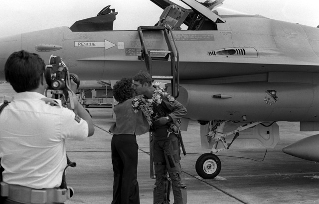 Upon his arrival in Hawaii, the pilot of this Air Force F-16A Fighting Falcon aircraft who has just landed, receives the traditional ring of flowers around his neck and a kiss from a pretty lady. The F-16A is from the 428th Tactical Fighter Squadron located at Nellis Air Force Base, Nevada, and is here to fly with Marine F-4 Phantom aircraft in support of Hawaii-based Army units. The event is a Joint Chiefs of STAFF exercise, which will last for one month (2 Oct to 2 Nov 1981)