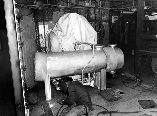 A welder works in the waste heat boiler No. 3 area aboard the destroyer HAYLER (DD-997). The ship, which is being built by Ingalls Shipbuilding, is presently 40 percent complete