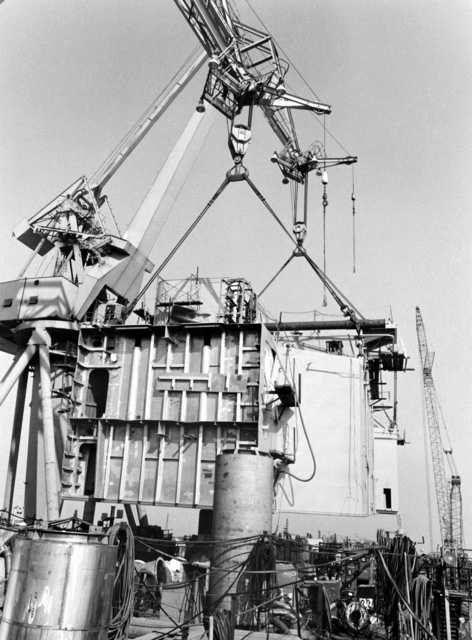The superstructure is lowered by crane onto the destroyer HAYLER (DD-997) during construction by Ingalls Shipbuilding. The ship is 40 percent complete