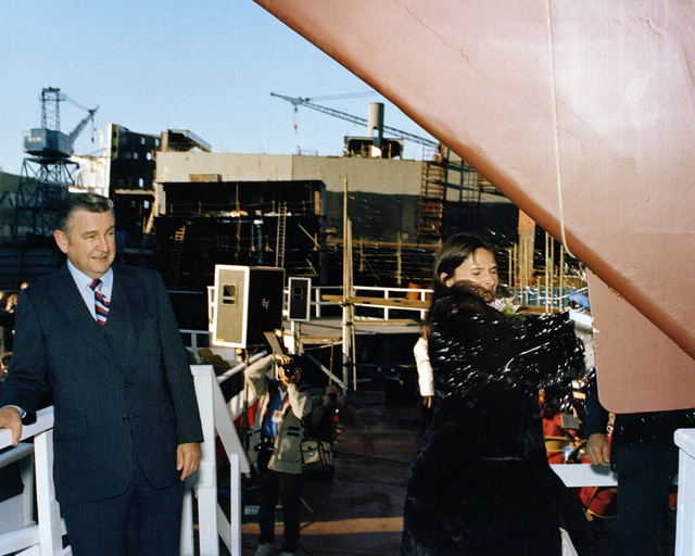 Mrs. Fracesca Ferguson, sponsor, breaks a bottle of champagne across the bow of the Oliver Hazard Perry class guided missile frigate USS AUBREY FITCH (FFG 34) at the conclusion of its launch ceremony. John Sullivan Jr., president of Bath Iron Works, is standing behind her