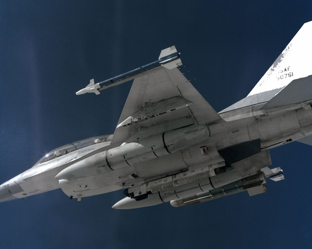 An air-to-air left underside view of an F-16B Fighting Falcon aircraft with a glide bomb mounted on the right outboard wing pylon, AIM-9 Sidewinder missiles on the wingtips, and an AN/ALQ-119 Electronic Countermeasures (ECM) pod on the fuselage centerline
