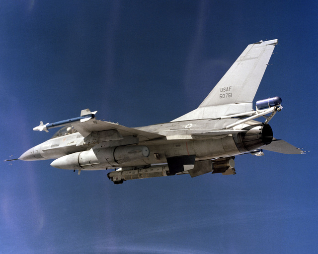 An air-to-air left rear view of an F-16B Fighting Falcon aircraft with a glide bomb mounted on the right wing pylon, AIM-9 Sidewinder missiles on the wingtips, and an AN/ALQ-119 Electronic Countermeasures (ECM) pod on the fuselage centerline. A spin-control parachute container is attached to the aircraft`s tail section