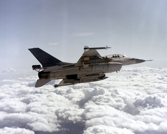 An air-to-air right side view of an F-16B Fighting Falcon aircraft with a glide bomb mounted on the right outboard wing pylon, AIM-9 Sidewinder missiles on the wingtips, and an AN/ALQ-119 Electronic Countermeasures (ECM) pod on the fuselage centerline. A spin-control parachute container is attached to the aircraft`s tail section
