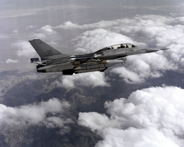 An air-to-air right side view of an F-16B Fighting Falcon aircraft with a glide bomb mounted on the right wing pylon, an AIM-9 Sidewinder missile on the wingtip, and an AN/ALQ-119 Electronic Countermeasures (ECM) pod on the fuselage centerline. A spin-control parachute container is attached to the aircraft`s tail section