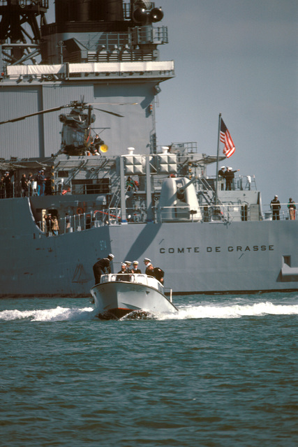 A stern view of the destroyer USS COMTE DE GRASSE (DD 974) with an SH-2F Seasprite helicopter aboard during re-enactment of the Battle of Yorktown. The captain's gig from the guided missile cruiser USS JOSEPHUS DANIELS is in the foreground. (SUBSTANDARD)