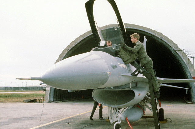 A ground crewman assists a pilot out of his F-16 Fighting Falcon aircraft. The aircraft is assigned to the 8th Tactical Fighter Wing