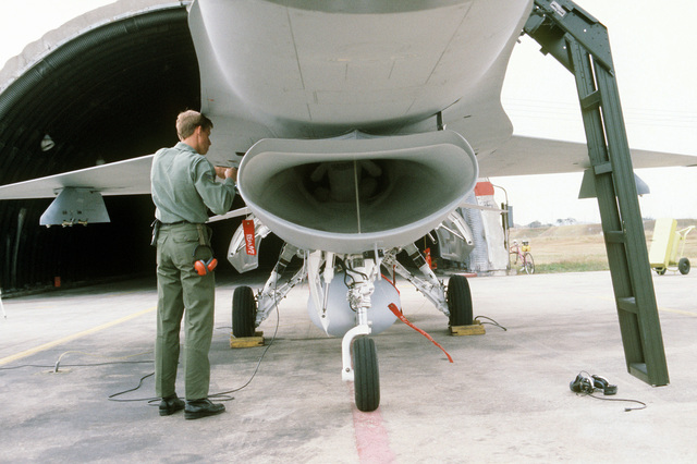 A ground crewman performs maintenance on an F-16 Fighting Falcon aircraft as a specialist works on the interior of the intake. The aircraft is assigned to the 8th Tactical Fighter Wing