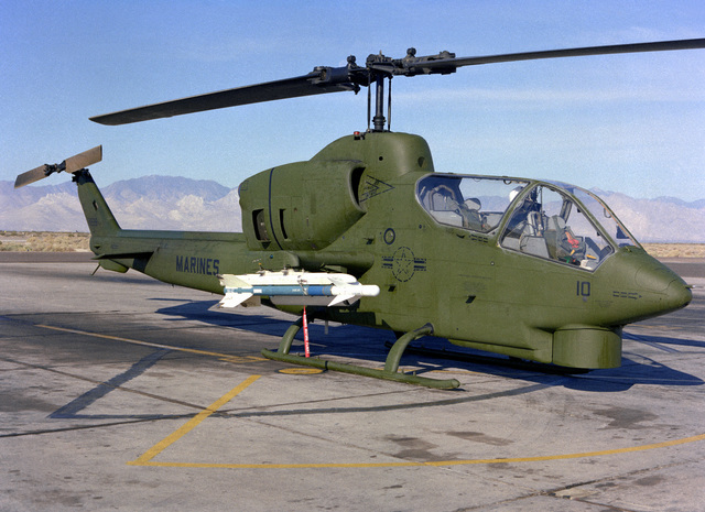 A right side view of an AH-1 Sea Cobra helicopter armed with a Sidearm missile