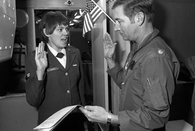 SRA Cathy J. Beverly of the 10th Airborne Command and Control Squadron is reenlisted by her commander, LTC Charles E. Hogan. SRA Beverly was the first woman to reenlist aboard the 10th ACCS