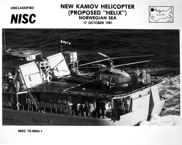 An air-to-air left side view of a Soviet Helix helicopter on the helicopter pad of the Soviet guided missile destroyer USSR UDALOY (DDG-480) as crewmen stand nearby. The Kamov-built helicopter has anti-submarine capabilities