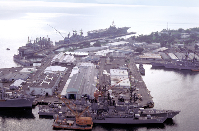An aerial view of ships in the harbor. In foreground, the frigate USS HAROLD E. HOLT (FF-1074), the destroyer USS O'BRIEN (DD-975) and the combat stores ship USS SAN JOSE (AFS-7); right, the guided missile cruiser USS HALSEY (CG-23) and the guided missile frigate USS BROOKE (FFG-1) bow to bow with the Filipino corvette RPS RIZAL (PS-69); and, background, the aircraft carrier USS KITTY HAWK (CV-63) with the guided missile cruiser USS STERETT (CG-31), the destroyer USS INGERSOLL (DD-990) and oilers USNS MISPILLION (T-AO-105) and USNS NAVASOTA (T-AO-106) astern