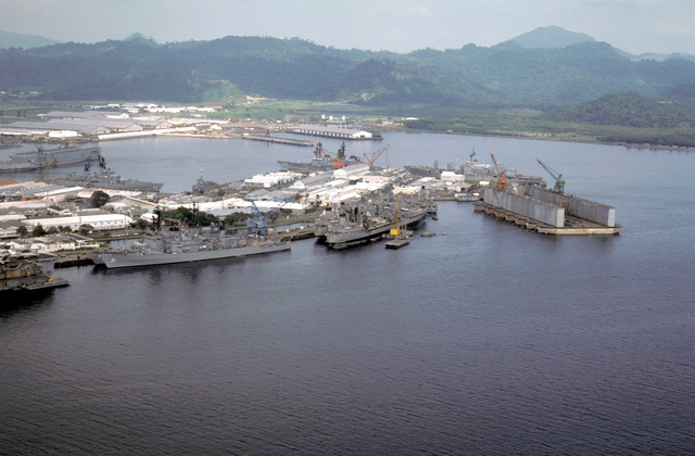 An aerial view of the harbor with docked ships including the guided missile cruiser US STERETT (CG-31), the destroyer USS INGERSOLL (DD-990), next to the STERETT, the oilers USNS NAVASOTA (T-AO-106) and USNS MISPILLION (T-AO-105), astern of the STERETT, the guided missile cruiser USS HALSEY (CG-23) and the destroyer USS O'BRIEN (DD-975)