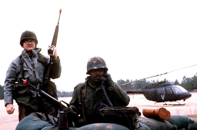 Sergeant Ellis Parks and AIRMAN 1ST Class John A. Denton guard the flight line entry control point during exercise BOLD EAGLE '82. The men are armed with M16 rifles