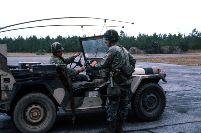 Sergeant John Ross and AIRMAN 1ST Class John A. Denton guard the flight line entry control point from a jeep during exercise BOLD EAGLE '82