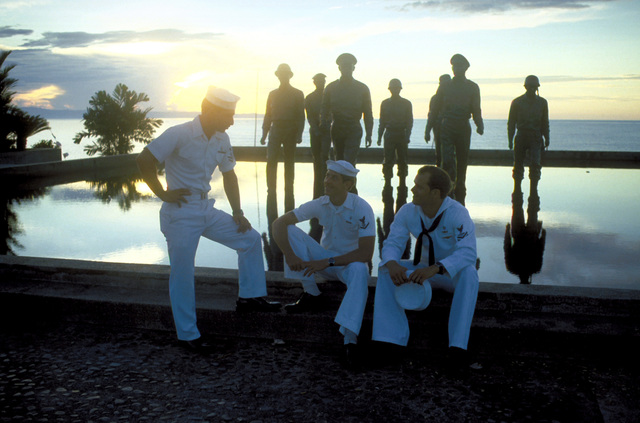 Silhouetted view as three crewmen from the salvage ship USS CONSERVER (ARS-39) relax in front of the life-like monument commemorating GEN Douglas MacArthur's re turn here on Oct 20, 1944. The CONSERVER and its crew were invited here to participate in ceremonies honoring that event of 37 years ago