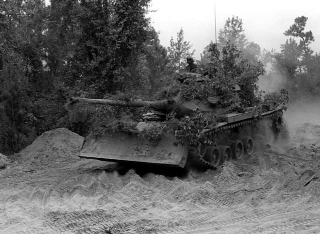 A camouflaged M-60A1 tank from the 8th Marines, equipped with a bulldozer blade, advances during an exercise
