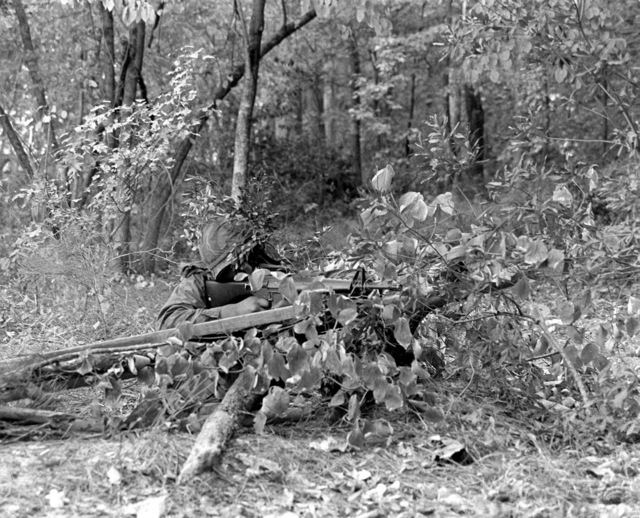 A member of the 8th Marines wearing protective clothing prepares to defend his camouflaged gun position during a gas attack drill. The Marine is armed with an M-16A1 rifle