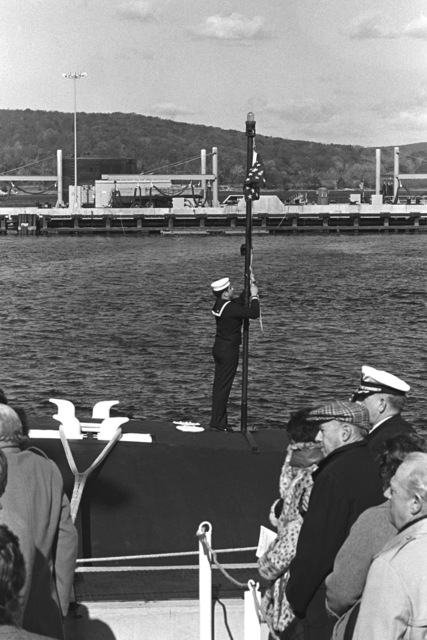 A crewman raises the union jack during the commissioning of the nuclear-powered attack submarine USS LA JOLLA (SSN 701)