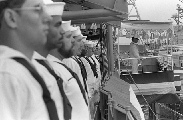 Crewmen man the rails near the speakers platform during the commissioning ceremony for the guided missile destroyer USS SCOTT (DDG-995). The speaker at the podium is CAPT Sebastian P. Passantino, supervisor of shipbuilding