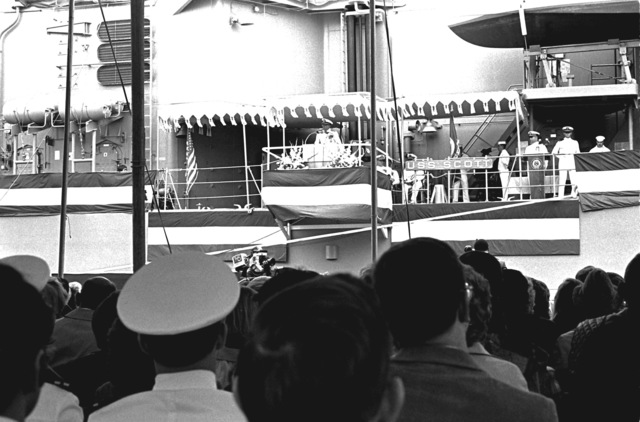 Spectators watch as VADM John D. Johnson Jr., commander, Naval Surface Force, U.S. Atlantic Fleet, speaks from the platform during the commissioning of the guided missile destroyer USS SCOTT (DDG-995)