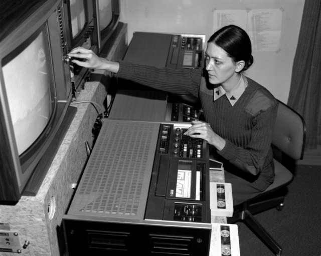 Woman Marine CPL. Kathy Sodek, a television editor, is operating a Sony 3/4-inch video tape editing machine, as she adjusts a television monitor. She is a member of the Training and Audiovisual Support Center