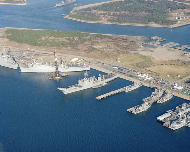 An aerial view of various ships and service craft, including the tank landing ship USS LA MOURE COUNTY (LST 1194), center, the dock landing ship USS PORTLAND (LSD 37) and the amphibious transport dock USS NASHVILLE (LPD 13), left, moored at the Naval Amphibious Base, Little Creek