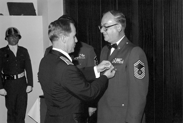 BGEN David L. Nichols (left), presents CMSGT Thomas Dempsey with a meritorious service medal during his retirement dinner