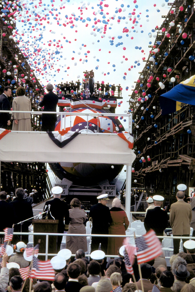 A rear view of distinguished guests on the speakers platform as they watch the nuclear-powered attack submarine NORFOLK (SSN-714) slide down the ways amid a barrage of just-released red, white, and blue balloons