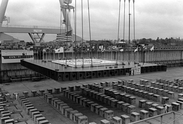 As part of the ceremony for the keel laying of the nuclear-powered aircraft carrier THEODORE ROOSEVELT (CVN-71), the keel is lowered by a crane to sit on a series of blocks at Newport News Shipbuilding. The ship is slated for delivery early in 1988, and will join three other nuclear-powered aircraft carriers (CVN-65, -68, AND -69) now in operation
