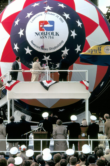 Flag officers and distinguished guests look toward the bow of the nuclear-powered attack submarine NORFOLK (SSN-714) as Sponsor Jane Weinberger launches the ship. Standing near Mrs. Weinberger are her husband, Secretary of Defense Caspar Weinberger, left, and Newport News Shipbuilding President Edward J. Campbell