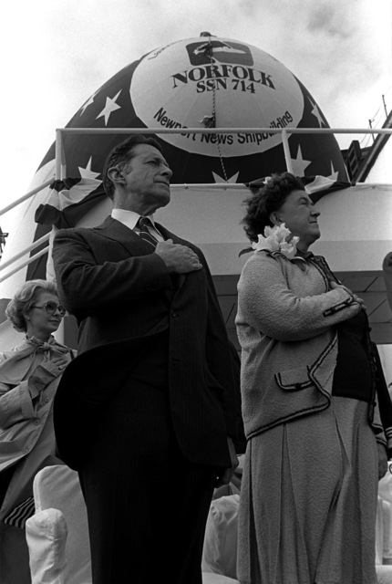 Secretary of Defense and Mrs. Caspar Weinberger stand during the playing of the national anthem at the launching of the nuclear-powered attack submarine NORFOLK (SSN-714). Mrs. Weinberger is sponsor of the submarine, which was built by Newport News Shipbuilding