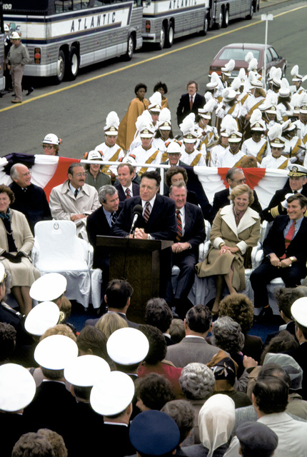 The audience and distinguished guests on the speaker's platform listen as Secretary of Defense Caspar Weinberger speaks at the keel laying of the nuclear-powered aircraft carrier THEODORE ROOSEVELT (CVN-71). Included on the platform are Mrs. Weinberger, far left, ship's sponsor, and Secretary of the Navy John F. Lehman Jr., far right