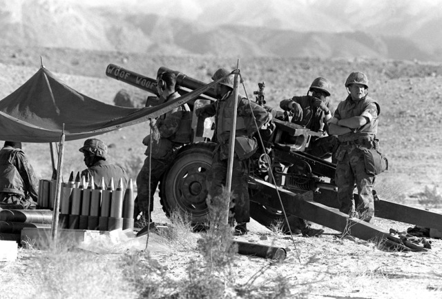 A 105mm howitzer team from Btry. H, 1ST Bn., 10th Marines, stands by for the next fire mission. The battery is participating in Operation CAX-1-2-82