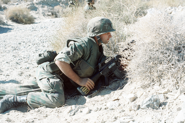 A combat-ready Marine, armed with an M-16A1 rifle, is partly in the prone position as he and the rest of his fire team assault an enemy bunker. The Marines are participating in Operation CAX 1-2-82 at the Marine Corps Air-to-Ground Combat Center
