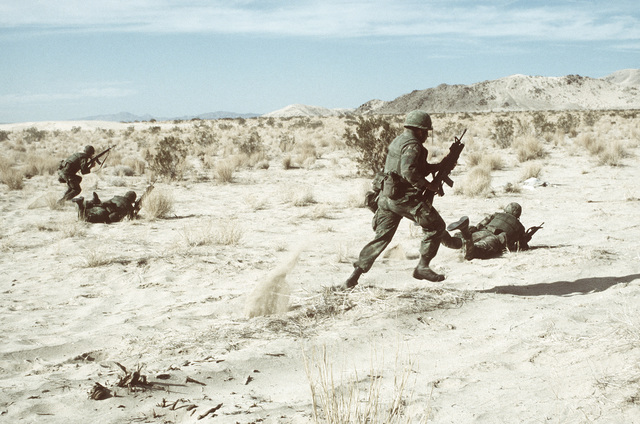 A combat-ready Marine fire team runs and hits the deck as they assault an enemy position. This is part of Operation CAX 1-2-82, held at the Marine Air-to-Ground Combat Center