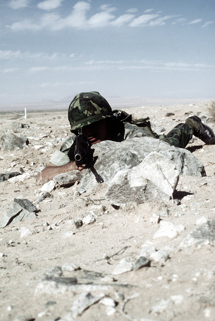 A combat-ready Marine, LCPL Jones, armed with an M-16A1 rifle, is in the prone position behind a rock to shield his body from possible enemy fire. The Marine is a participant in Operation CAX 1-2-82 at the Marine Corps Air-to-Ground Combat Center