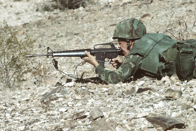 A combat-ready Marine, PFC Jones, fires his M-16A1 rifle from a prone position at a bunker during Operation CAX 1-2-82 at the Marine Corps Air-to-Ground Combat Center