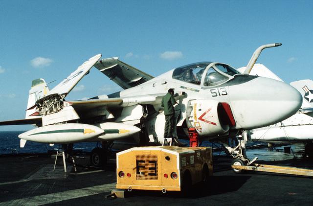 A crewman services an A-6E Intruder aircraft on the flight deck of the aircraft carrier USS MIDWAY (CV 41)
