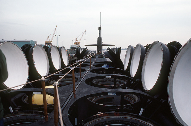 A deck view, looking toward the bow, of the nuclear-powered ballistic missile submarine OHIO (SSBN-726) with its missile tubes opened during precommissioning activities. The submarine, built by General Dynamics Corp., carries Trident C-4 (UGM-96) submarine-launched ballistic missiles