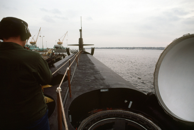 A deck view, looking toward the bow, of the nuclear-powered ballistic missile submarine OHIO (SSBN-726) with a crewman on its deck and its missile tubes open during precommissioning activities. The submarine, built by General Dynamics Corp., carries TRIDENT C-4 (UGM-96) submarine-launched ballistic missiles (SLBMs)