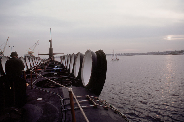 A deck view, looking toward the bow, of the nuclear-powered ballistic missile submarine OHIO (SSBN-726) with crewmen on deck and missile tubes opened during precommissioning activities. The submarine, built by General Dynamics Corp., carries TRIDENT C-4 (UGM-96) submarine-launched ballistic missiles (SLBM)