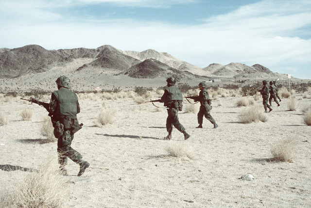 A line of Marines from Co. B, 1ST Bn., 8th Marines, 2nd Marine Div., walk toward an enemy position. The Marines are participating in Operation CAX 1-2-82 at the Marine Corps Air-to-Ground Combat Center