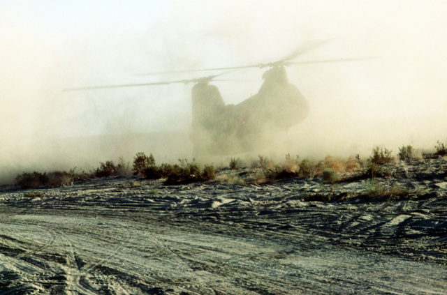 A Marine CH-46 Sea Knight helicopter sits down in a cloud of dust. The helicopter is bringing Marines in to participate in Operation CAX 1-2-82 at the Marine Corps Air-to-Ground Combat Center