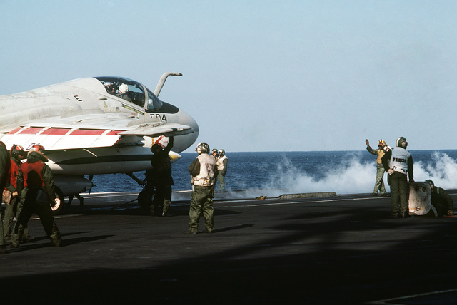 A plane director aboard the aircraft carrier USS MIDWAY (CV 41) guides an A-6E Intruder aircraft onto a catapult