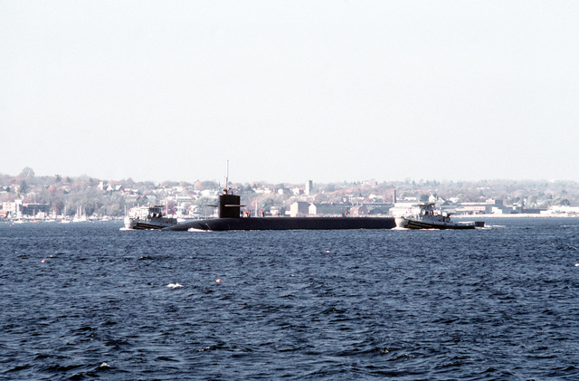 A port view of the nuclear-powered ballistic missile submarine OHIO (SSBN-726) being escorted by two large harbor tugs following its final sea trials before commissioning. The tugboats are the METACOM (YTB-829) and the NEGWAGON (YTB-834). The submarine was built by General Dynamics Corp
