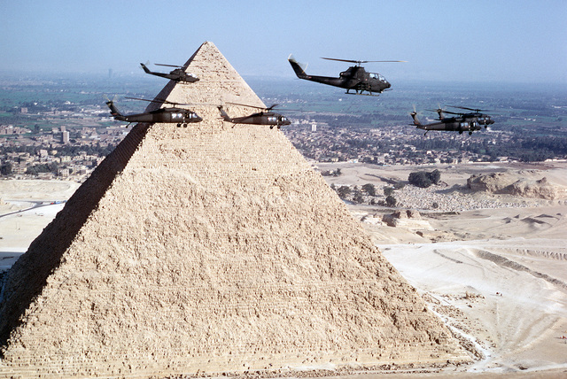 A right side view of UH-60 BlackHawk and AH-1G Cobra helicopters flying in front of a pyramid during exercise Bright Star '82