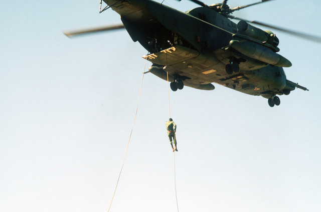 A soldier rappels from a hovering CH-53 helicopter during exercise Bright Star '82