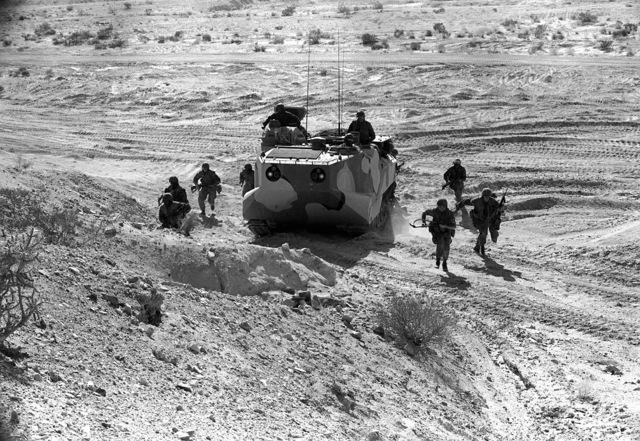 A squad of combat-ready Marines debark a personnel tracked landing vehicle 7 (LVTP-7) and climb a hill as part of the assault phase during Operation CAX-1-2-82