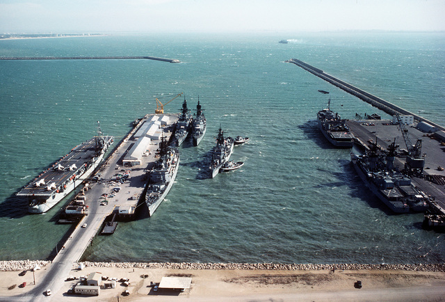 A view of ships docked at the pier as two tugboats nudge the destroyer USS JONAS INGRAM (DD-938) into docking position. The docked ships include the Spanish small aircraft carrier DEDALO (PA-01), left, and the guided missile cruiser USS WAINWRIGHT (CG-28), off the Ignoramus starboard bow